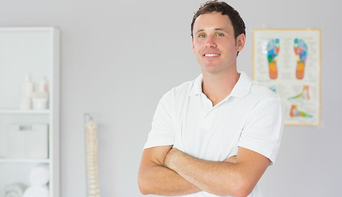 Handsome happy physiotherapist standing with arms crossed in bright office