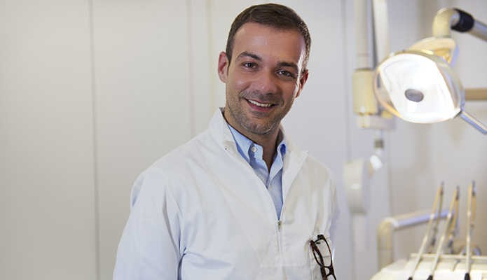 Portrait of happy caucasian dentist smiling at camera